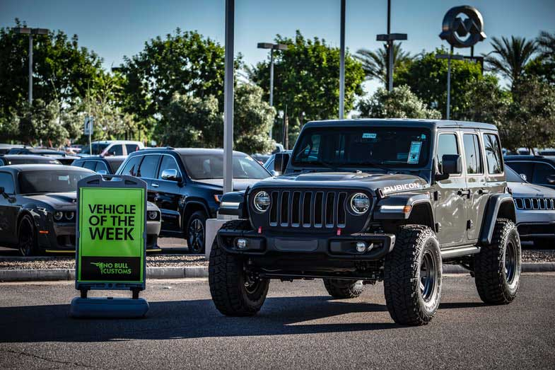 Black Jeep Wrangler Parked Beside a Vehicle of the Week Sign
