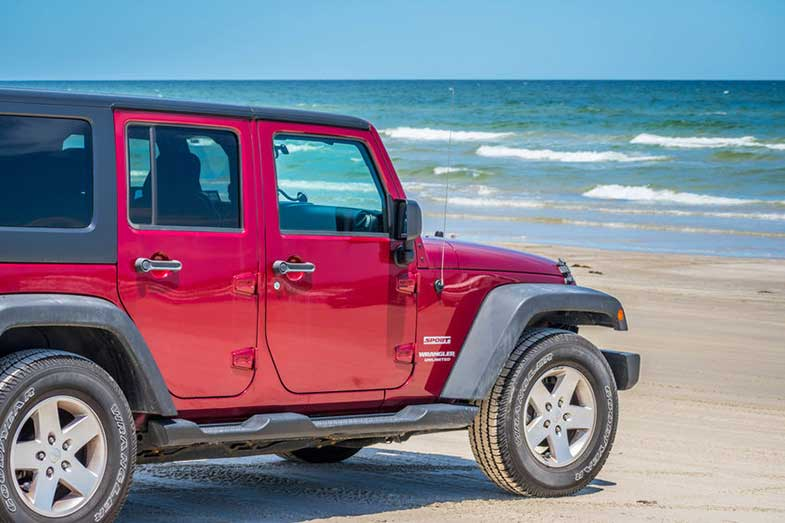 Red Jeep Wrangler Unlimited Sport Parked on the Beach