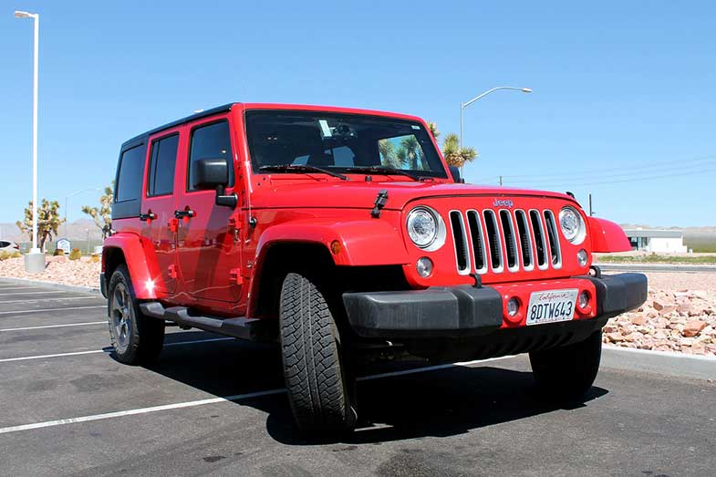 Red Jeep Wrangler in Parking Lot During the Day with California License Plate