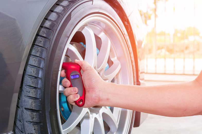 Checking Tire Air Pressure with Red Digital Gauge