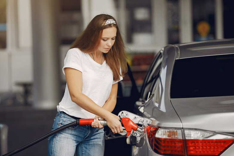 Focused Woman Refueling Car