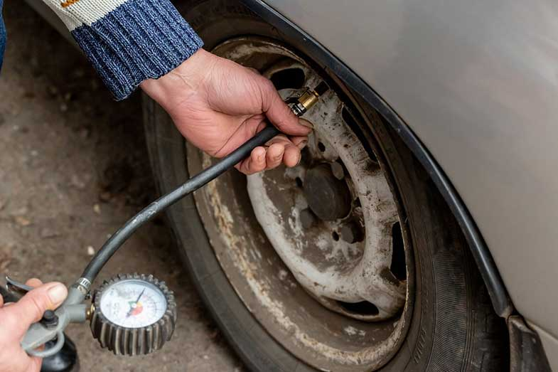 Man Checking Air Pressure and Filling Up the Tires with Air