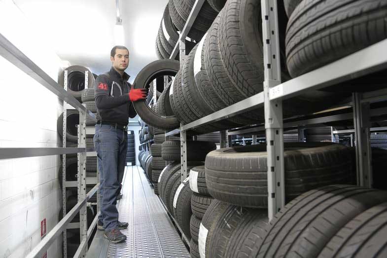 Man in Black Jacket Standing Beside Tires