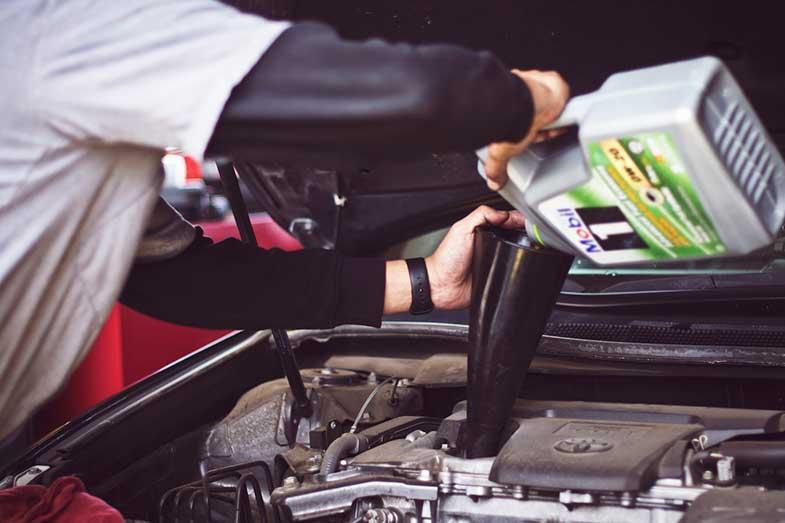 Man Refilling Motor Oil