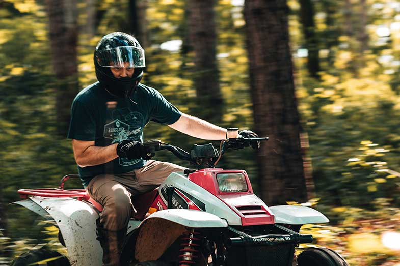 Man Riding ATV in Forest During the Day