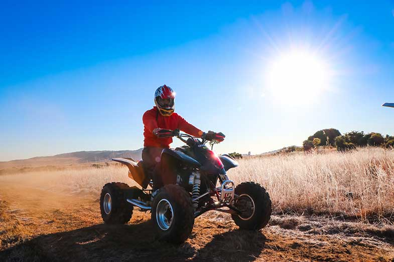 Man Riding ATV on Brown Path During Daytime