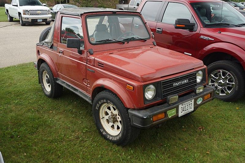 Red 1987 Suzuki Samurai on Grass