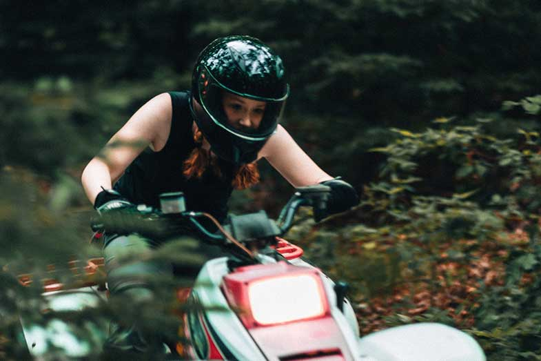 Woman Riding ATV in Forest