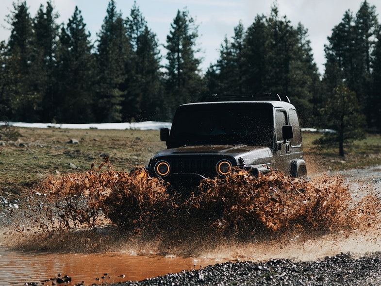 Black Off-Road Vehicle Driving Through Mud Puddle