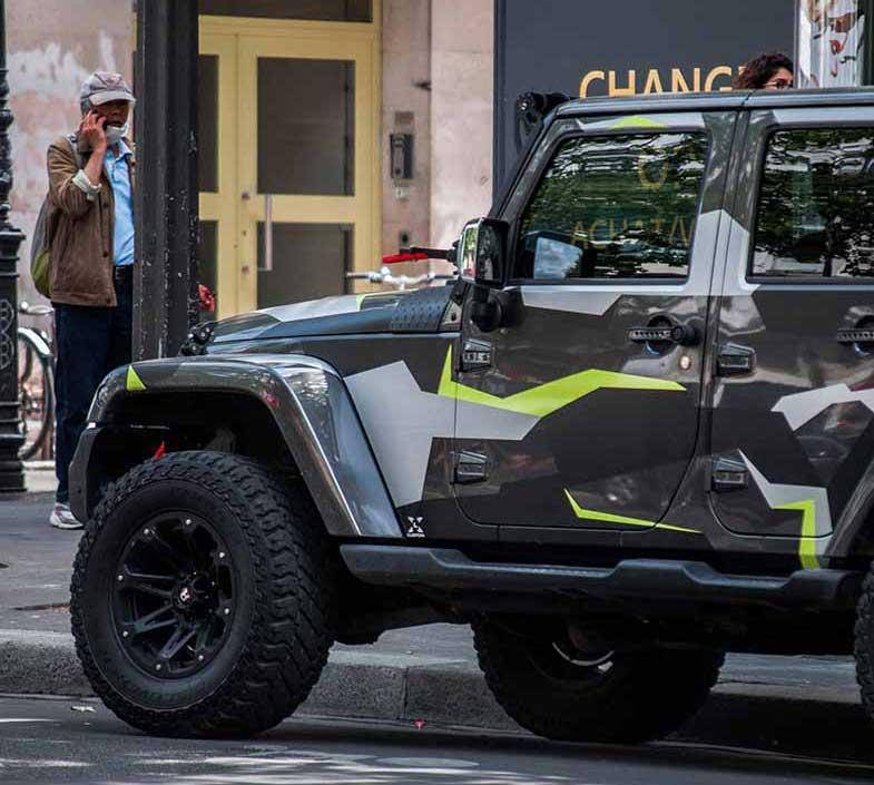 Green and Black Jeep Wrangler Parked Beside Sidewalk