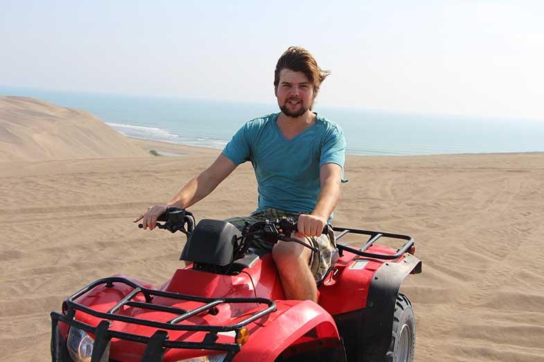 Man Riding ATV in Desert Sand