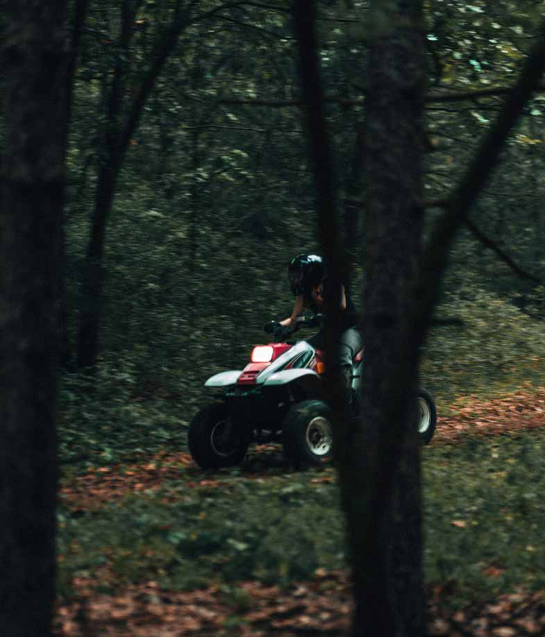 Person Riding Red and White ATV During Daytime