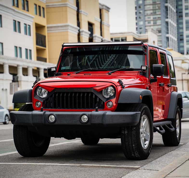 Red Jeep Wrangler on the Street During the Day