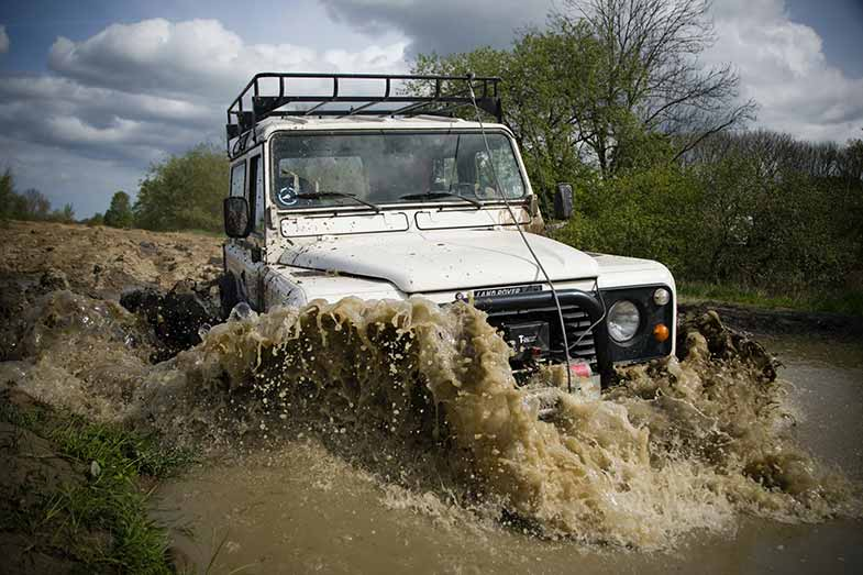 White Off-Road Vehicle Driving Through Water