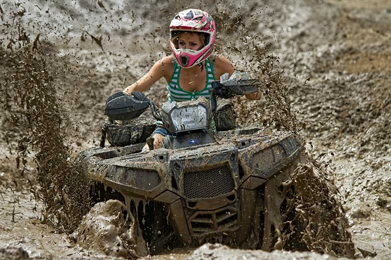 Woman Riding Off-Road ATV in Mud
