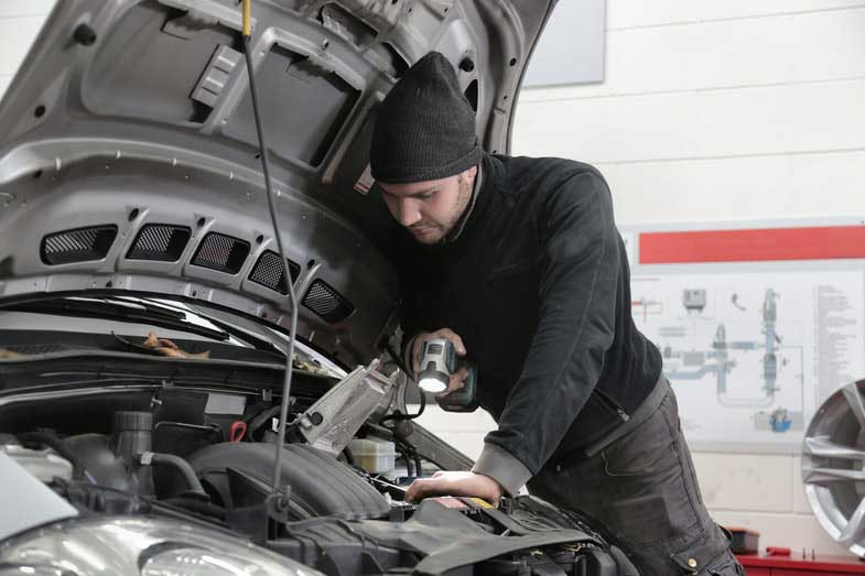 Man in Black Jacket Inspecting Car Engine