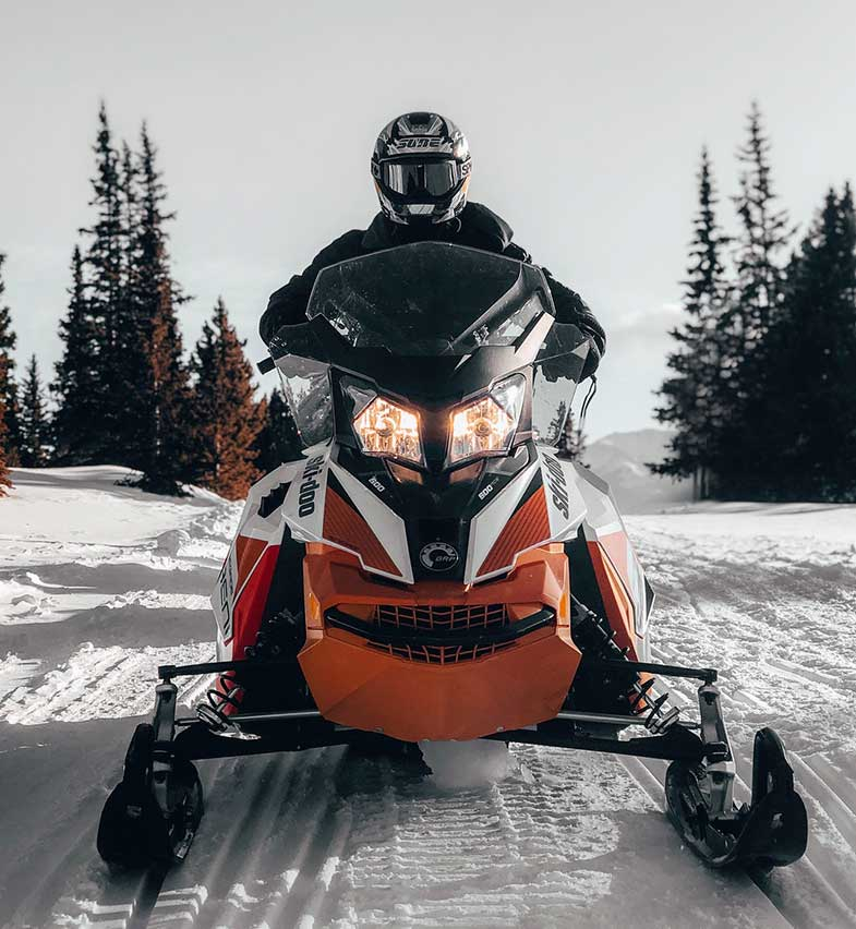 Person Riding Orange and White Snowmobile