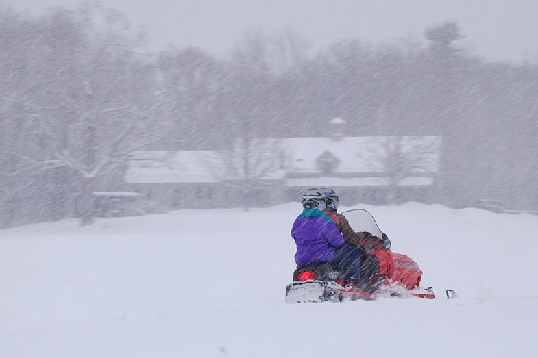 Two People Riding Snowmobile in Heavy Snowfall