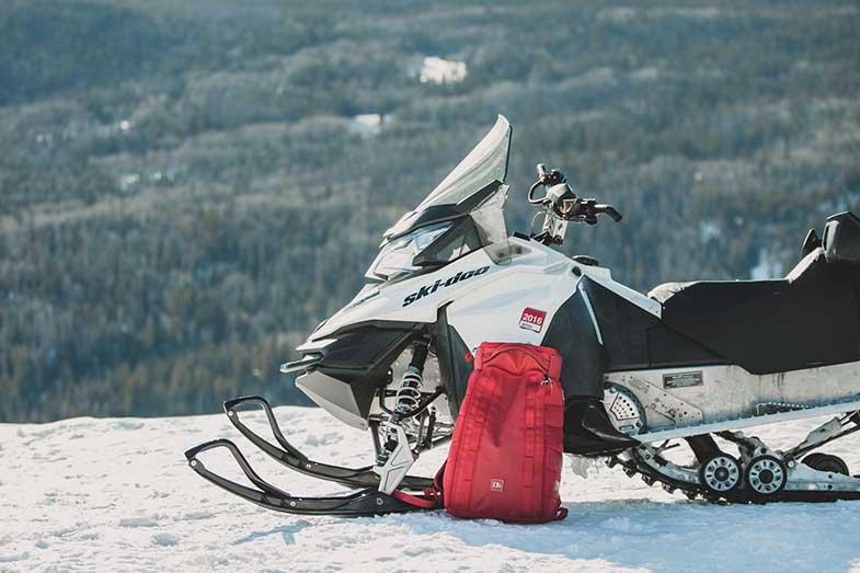 White and Black Snowmobile on a Mountain with Red Backpack