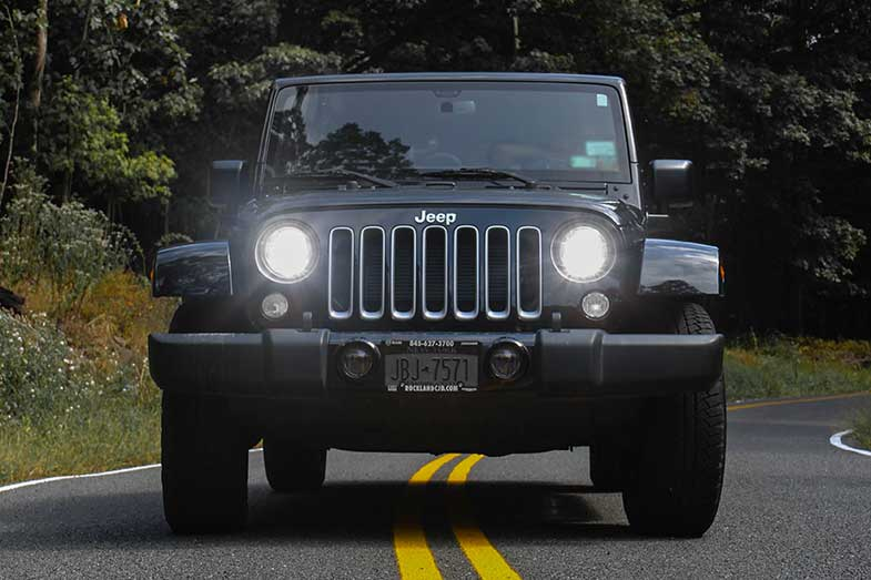 Black Jeep Wrangler Driving on Paved Road