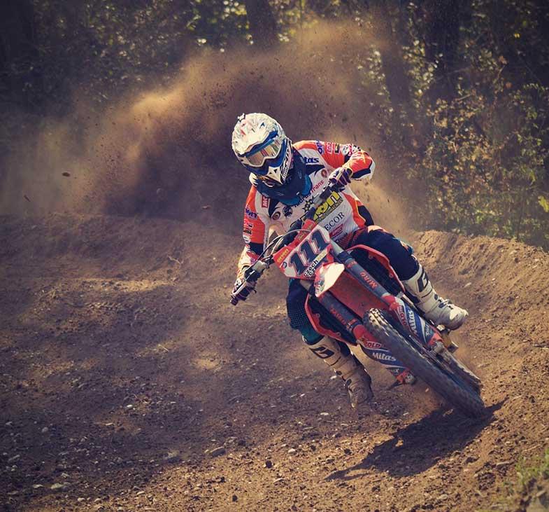 Dirt Bike Motocross Rider Turning Corner on Track