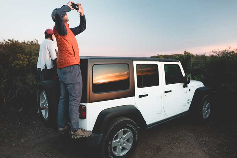 People Standing on Jeep Tailgate and Taking Photo