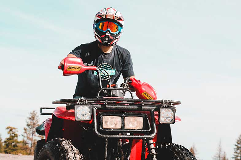 Person with Helmet and Goggles Riding Red ATV