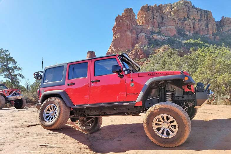 Red Jeeps Driving on Rocky Terrain