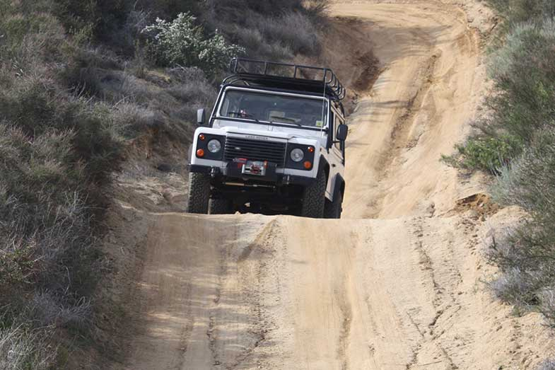 White Land Rover Off-Roading Down Hill