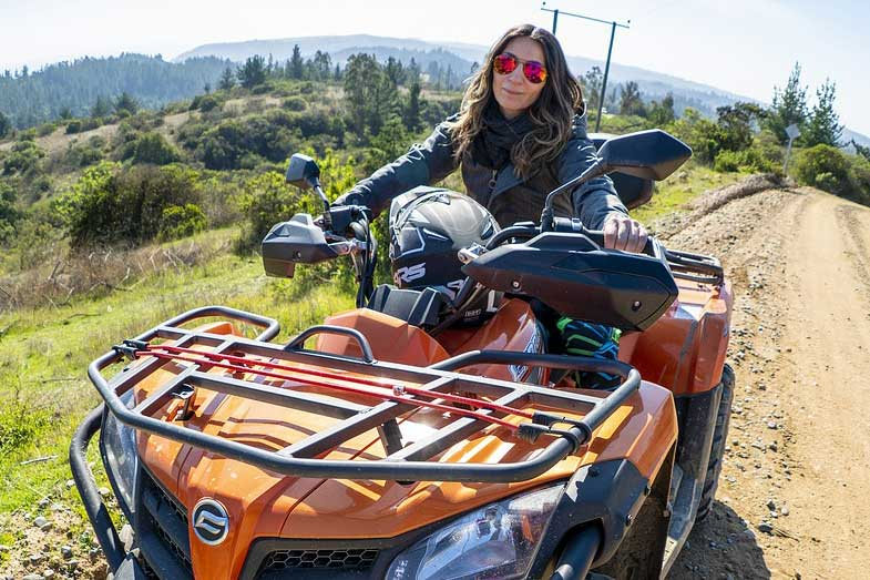 Woman Driving Orange ATV Quad on Dirt Road