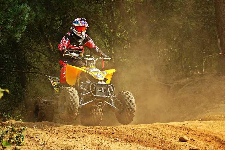 Yellow ATV Riding on Dusty Motocross Track