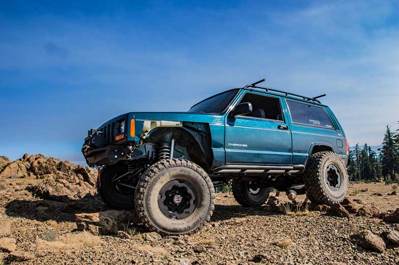 Blue Off-Road SUV Driving on Rocky Terrain