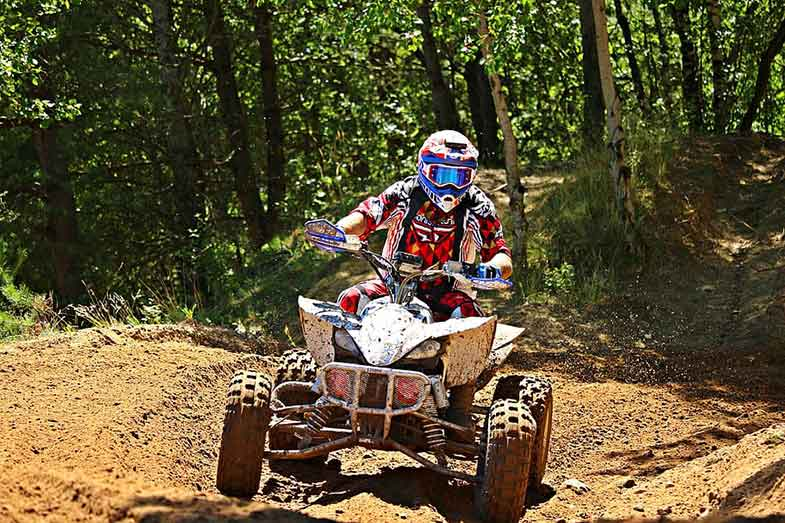 Riding ATV on Dirt Track by Trees