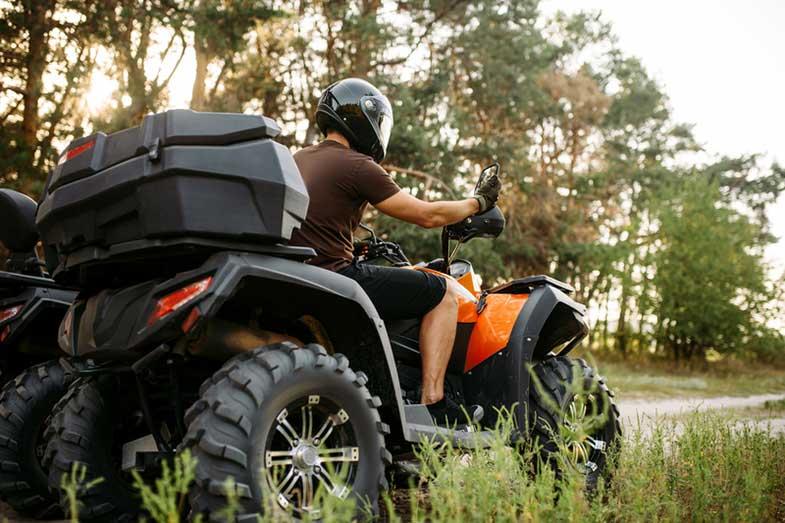 ATV Rider in Helmet and Equipment on Quad Bike