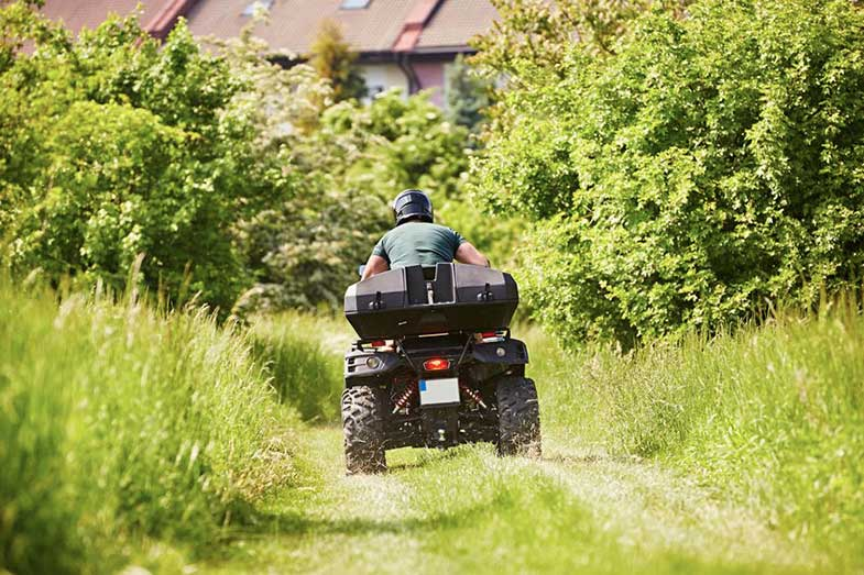 Person with Helmet Driving All-Terrain-Vehicle