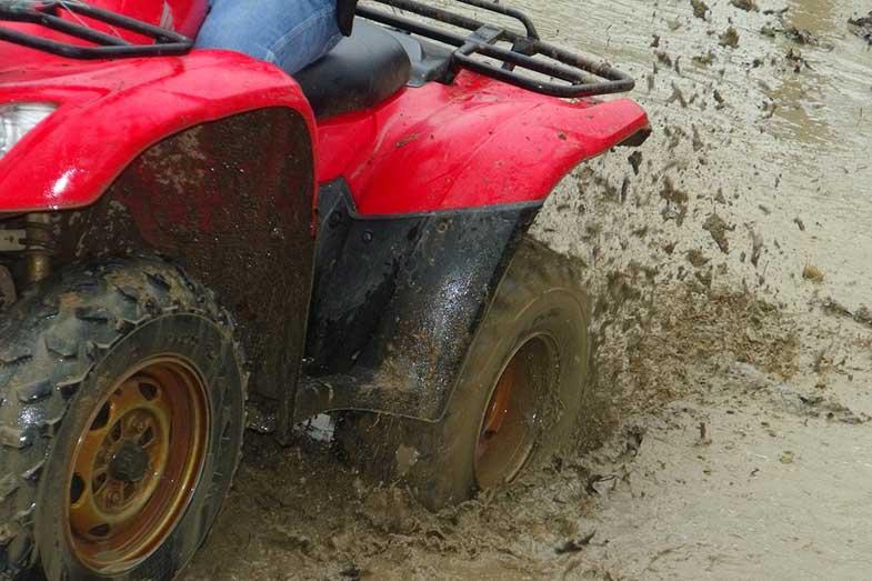 Red ATV Splashing Through Muddy Terrain