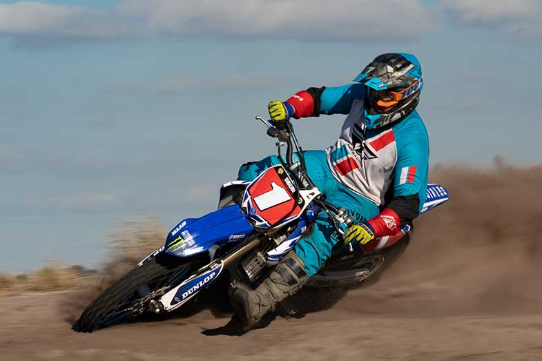 Dirt Bike Rider in Blue Turning Corner on Dirt Bike Track
