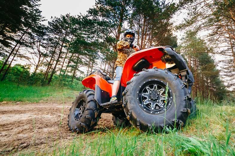 Man on ATV Quad Bike in Mud Track