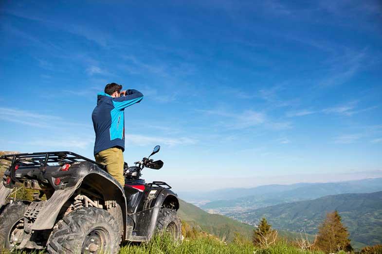 Man on ATV Quad Bike on Mountain Trail