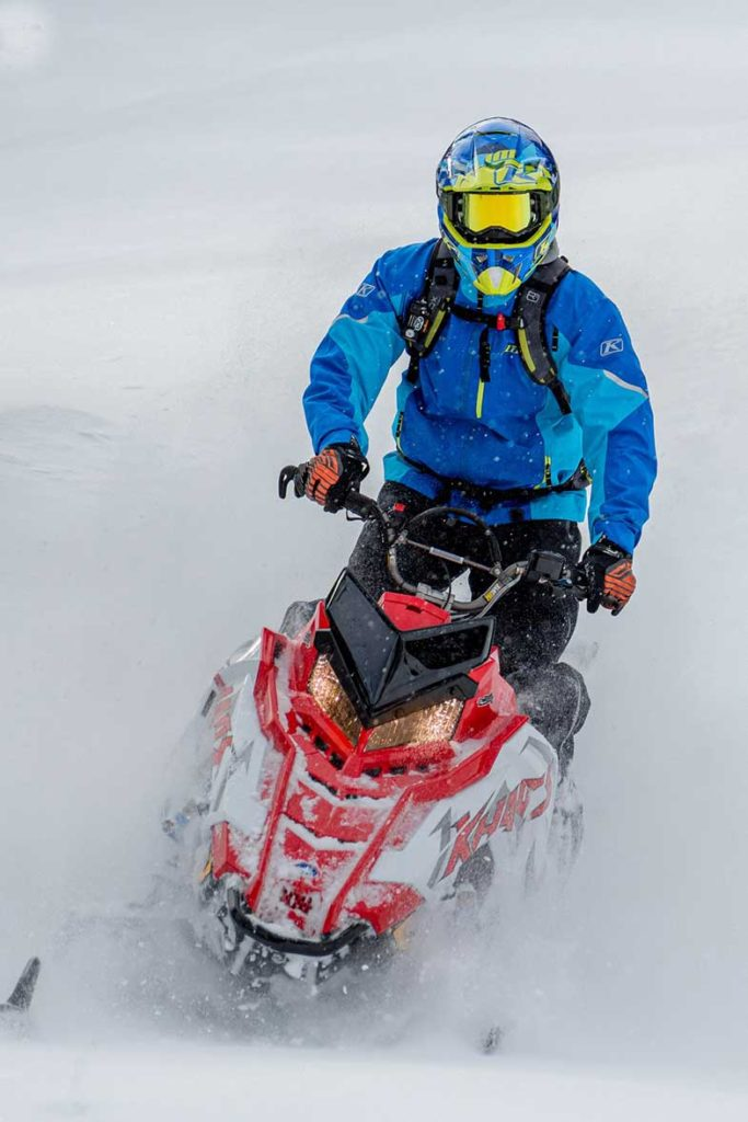 Person in Blue Jacket Riding Red Snowmobile