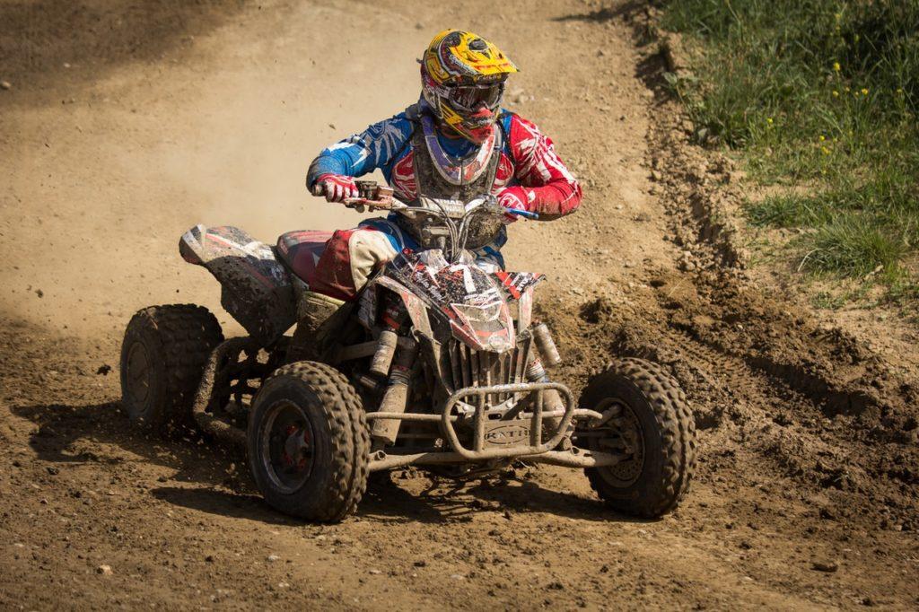 Person Riding Quadbike on Dirt Track