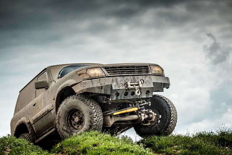 Off-Road Car Covered in Mud on Grass Hill