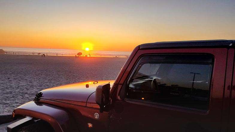 Red Jeep on the Beach During Sunset