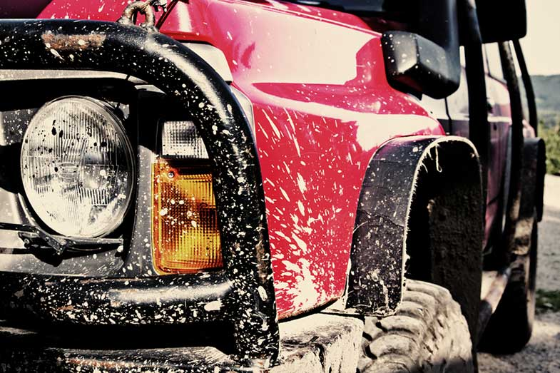 Red Off-Road Car Covered in Mud
