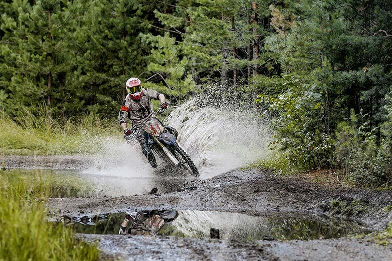Dirt Bike Rider Splashing Through Puddle