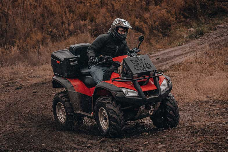 Person Riding a Red ATV on a Muddy Trail