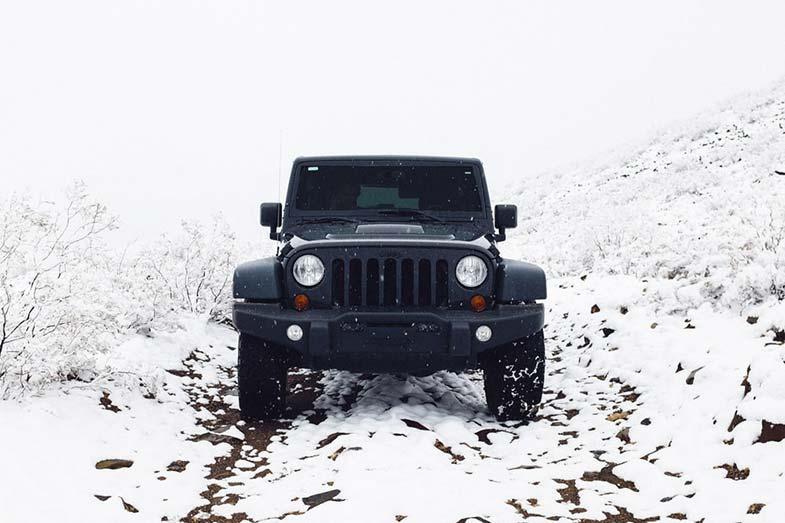 Black Jeep Wrangler Off-Road Snow Trail