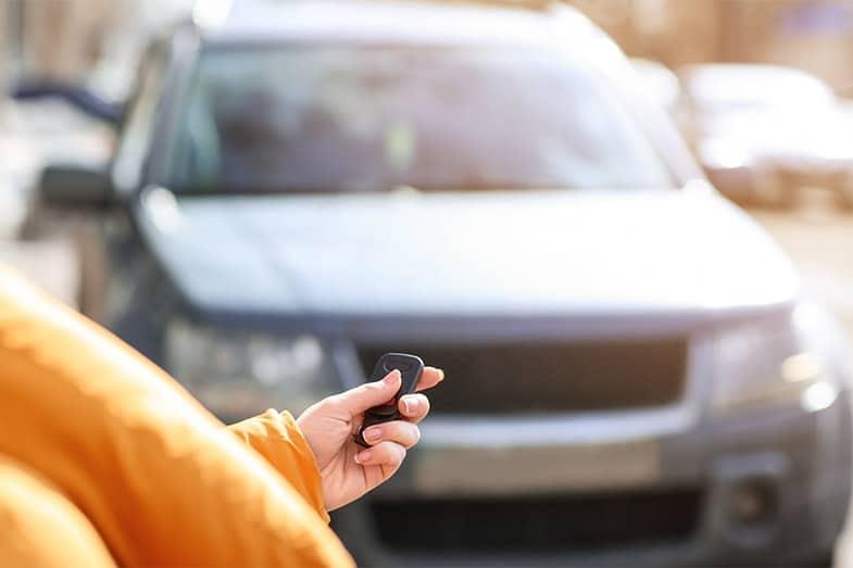 Person Using Key Fob to Turn Off Car Alarm