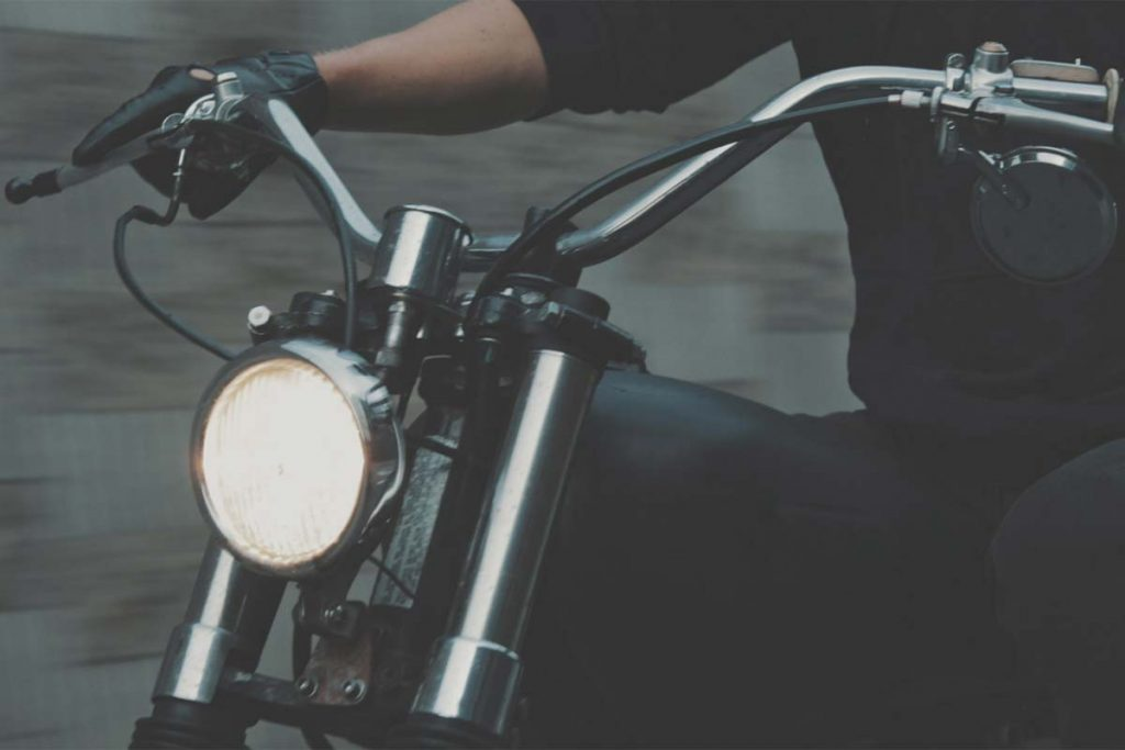 Person Riding Motorbike with Headlight on