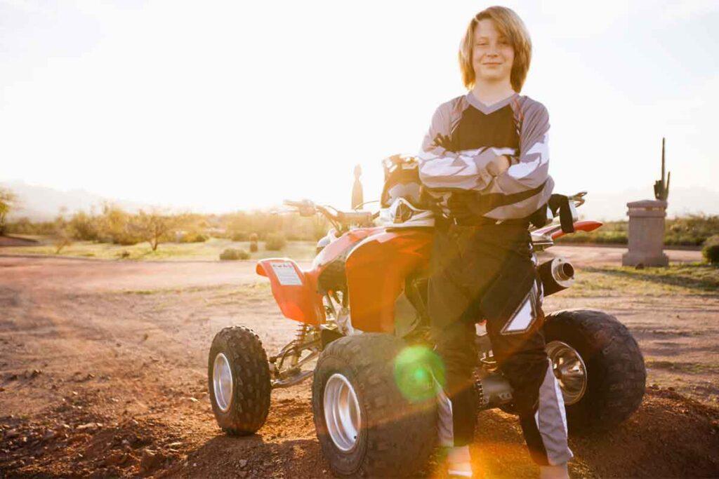 Boy Beside Red ATV